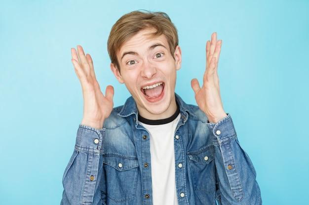 Молодой эмоциональный смешной мужчина-подросток в джинсовой рубашке на синем