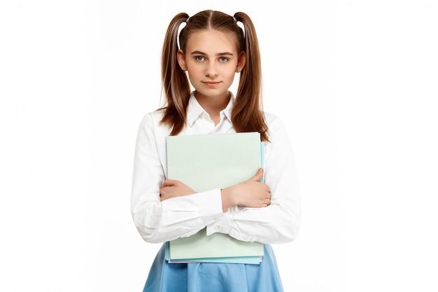 Молодая эмоциональная девушка в униформе позирует, изолированных на белой стене