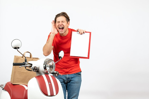 Young emotional happy smiling delivery guy in red uniform standing near scooter showing document on white wall