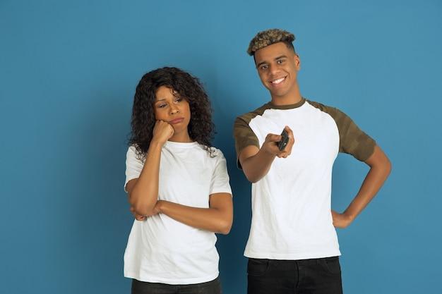 青でポーズをとる白いカジュアルな服を着た若い感情的な男性と女性。