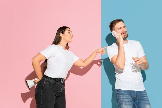 Молодой эмоциональный мужчина и женщина на розовой и синей стене