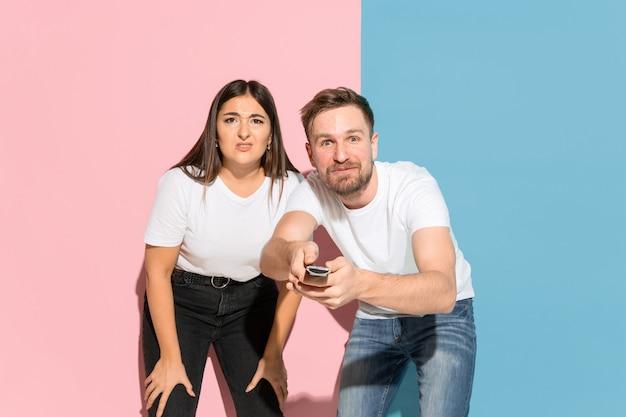 ピンクと青の壁に若い感情的な男と女