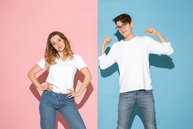 Молодой эмоциональный мужчина и женщина на розовом и синем