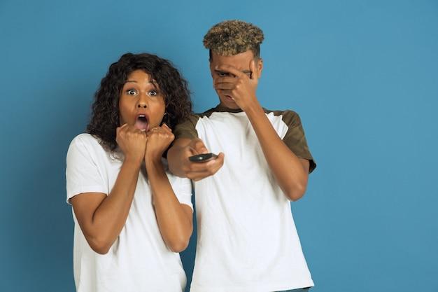 青でポーズをとる若い感情的な男性と女性。