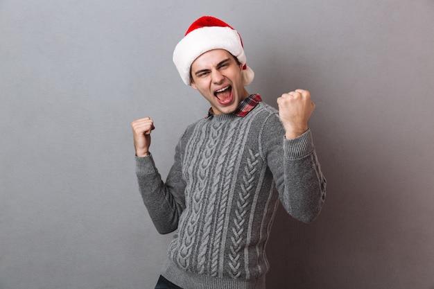 Молодой эмоциональный человек в шляпе санта-клауса