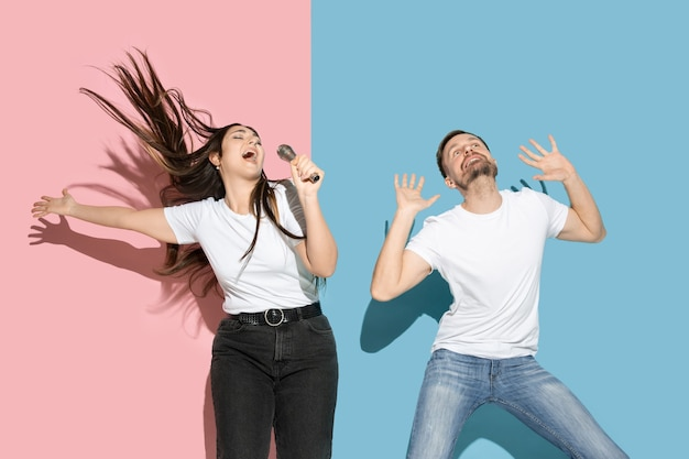 Young emotional man and woman on pink and blue wall