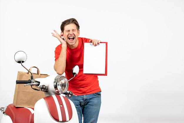 Giovane ragazzo di consegna nervoso emotivo in uniforme rossa in piedi vicino a scooter che mostra il documento che chiude un orecchio sul muro bianco