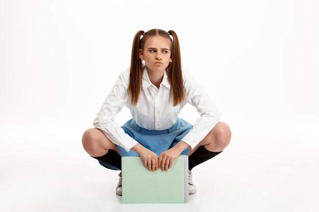 Молодая эмоциональная милая девушка в форме представляя над белой стеной