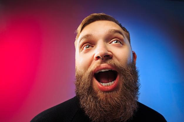 口を開けて立っている若い感情的な驚きのひげを生やした男。人間の感情、表情の概念。