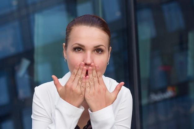 口を開けて立っているとカバーする若い感情的な驚きの実業家は、屋外、手のひらで顔を閉じます。ショックを受けた女性、オフィスの外のカメラを見て女の子。うわー!信じられない。