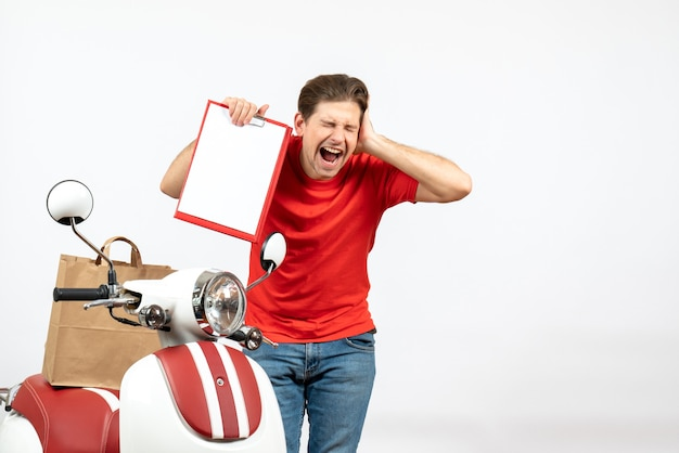 Young emotional troubled delivery guy in red uniform standing near scooter showing document and suffering from headache on white wall
