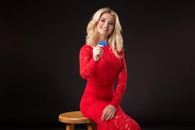 彼女の手にチップの束を保持している若い感情的な女性。ポーカー