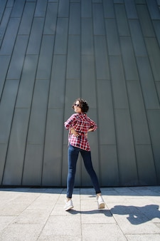 Young emotional woman in a jeans and white sneakers jumping by the wall on the city street. portrait of smiling girl with curly hair and sunglasses on gray wall