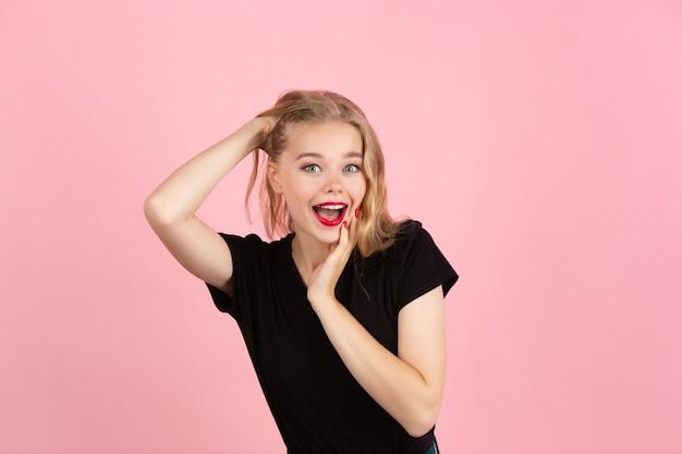 Молодая эмоциональная женщина на розовой стене студии человеческих эмоций выражение лица концепции
