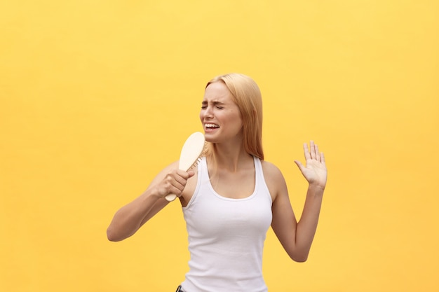 Young emotional woman singing with comb while dressing. isolated over yellow background.