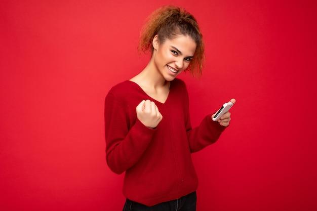 Молодая эмоциональная женщина в темно-красном свитере, изолированном над красным