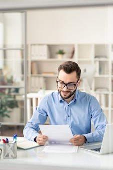 Young employee in blue shirt and eyeglasses looking through one of papers during working day in office