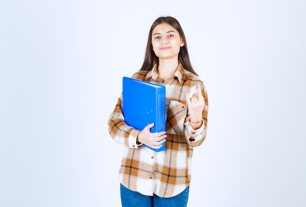 Young employee holding blue folder and standing on white wall.