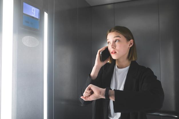 젊은 직원이 스마트 폰으로 말하는 엘리베이터의 층 번호를보고 있습니다.