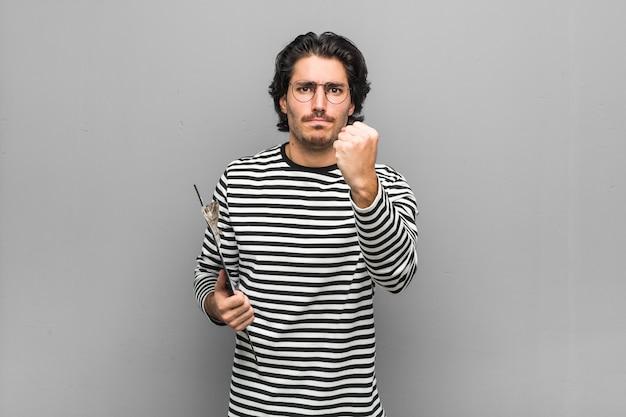 カメラ、積極的な表情に拳を示す目録を保持している若い従業員男。