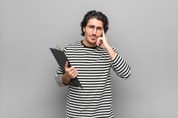 Young employee man holding an inventory focused on a task, keeping forefingers pointing head.