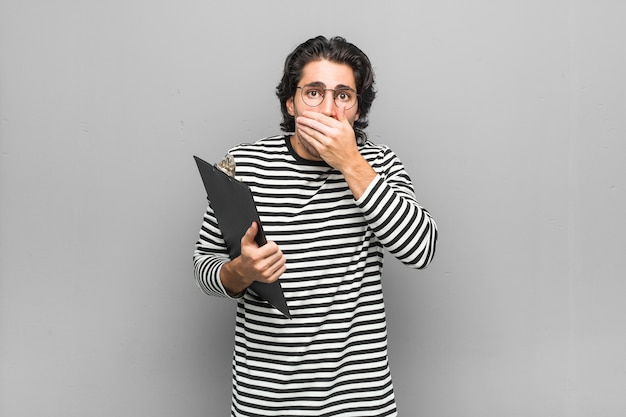 Young employee man holding an inventory shocked covering mouth with hands.