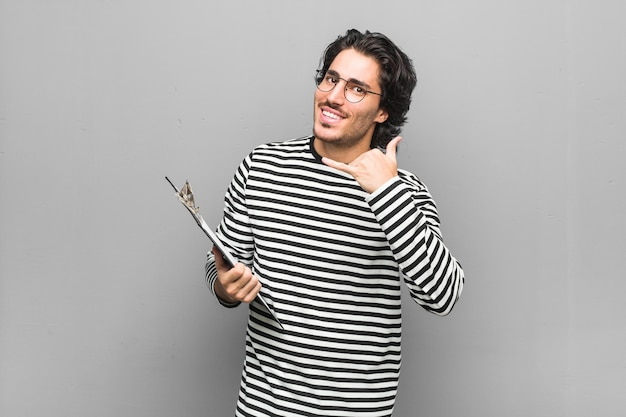 Young employee man holding an inventory showing a mobile phone call gesture with fingers.