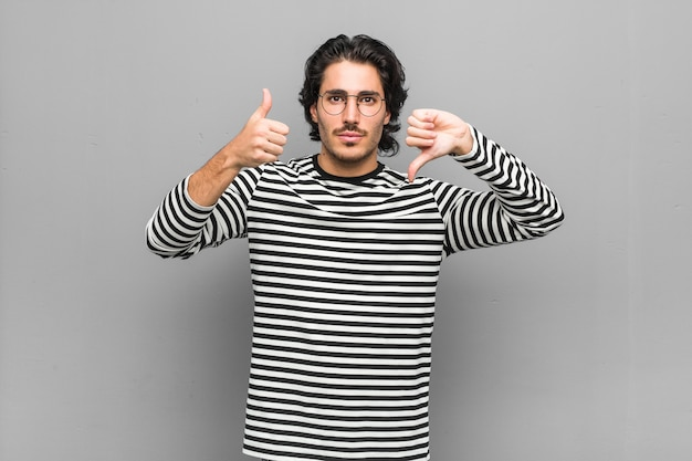 Young employee man holding an inventory showing thumbs up and thumbs down, difficult choose concept