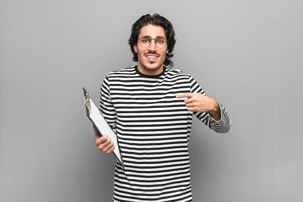 Young employee man holding an inventory surprised pointing with finger, smiling broadly.