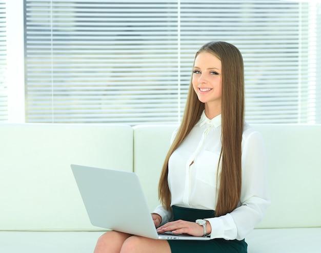 ノートパソコンでテキストを読んでいる会社の若い従業員