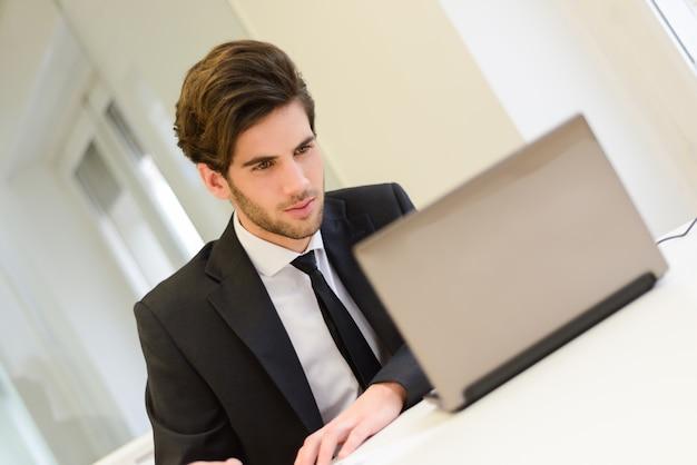 Молодой работник обращая внимание на экран компьютера