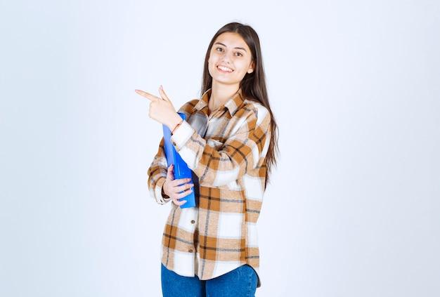 Giovane impiegato con cartella blu che punta al suo fianco sul muro bianco.