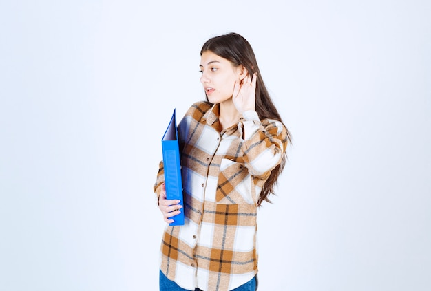 Giovane impiegato con la cartella blu che prova ad ascoltare qualcosa sulla parete bianca.