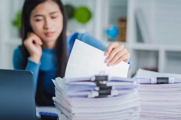 Молодая женщина работника вручает проверять стог бумажных файлов для искать незаконченный документ arheieve после того как отделка занята трудолюбивым.