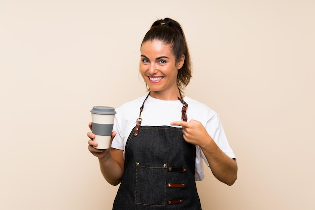 Young employee woman holding a take away coffee and pointing it