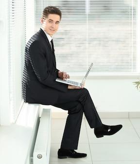 Молодой сотрудник, работающий на ноутбуке, сидя в коридоре офиса