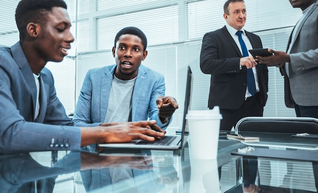 직장에서 온라인 뉴스를 논의하는 젊은 직원. 복사 공간 사진
