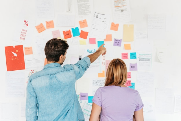 Молодые сотрудники, глядя на стену с маркетинговыми заметками