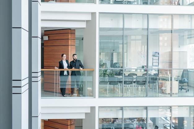 手すりに立って周りを見回すビジネスセンターの若い従業員、ガラス張りのオフィスルームのインテリア