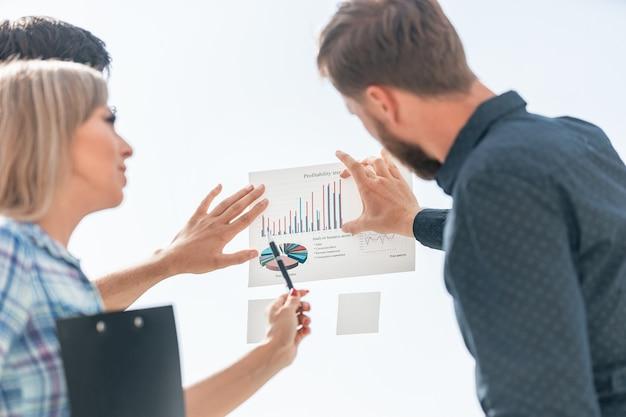 財務グラフにペンを指している若い従業員。ビジネスコンセプト