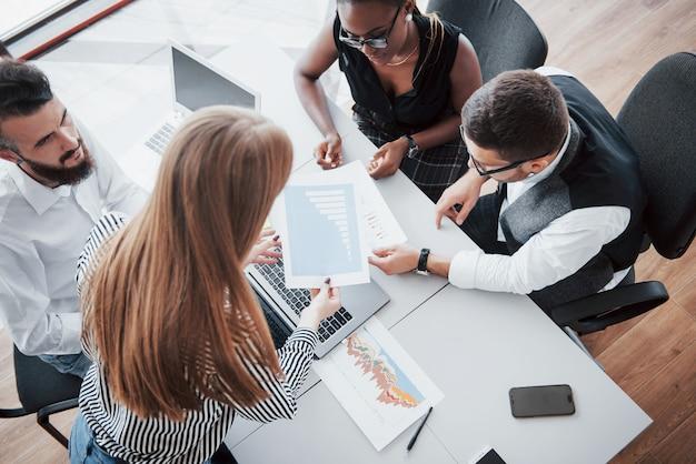Молодые работники сидя в офисе на таблице и используя компьтер-книжку, концепцию встречи метода мозгового штурма коллективной работы.