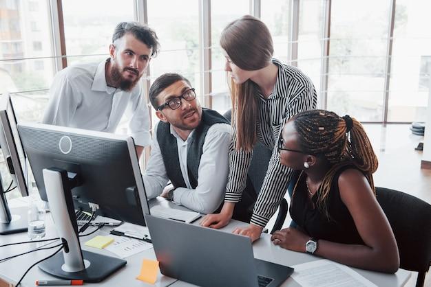 테이블에 사무실에 앉아 노트북을 사용하는 젊은 직원, 팀 작업 브레인 스토밍 회의 개념.