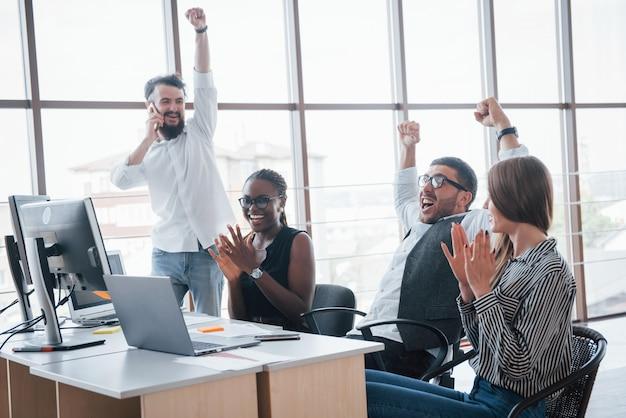 Молодые сотрудники сидят в офисе за столом и используют ноутбук