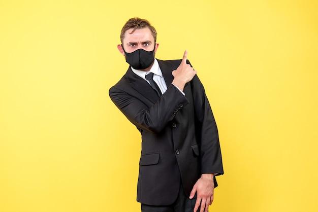 Il giovane datore di lavoro mostra il segno di attenzione un dito verso l'alto sul giallo