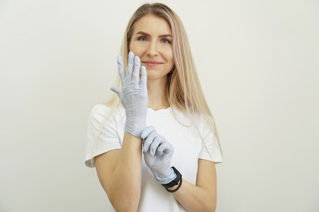 젊은 정력적인 아름 다운 소녀는 장갑에 넣습니다. 즐거운 친절한 여성이 고객을 기다리고 일을 준비하고 있습니다.