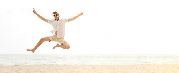 Young energetic happy tourist man jumping at the beach