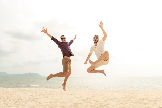 Young energetic happy tourist men jumping at the beach
