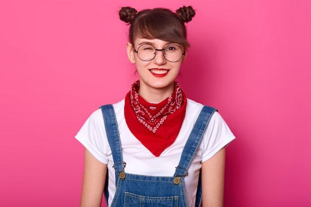 Giovane ragazza allegra positiva energetica in piedi isolato su rosa in studio, con un occhio chiuso