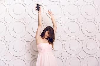 ヘッドフォンで音楽を聴いて踊る若いエネルギッシュな女性