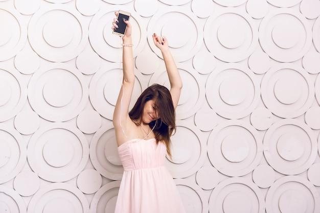 헤드폰에서 음악을 듣고 춤을 추는 젊은 활기찬 여자